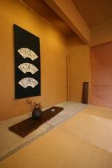 柿渋染めの建具、土壁、コンクリートの床板の和室