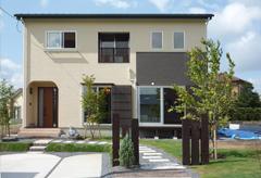 木の縦格子が緑と一体になった家